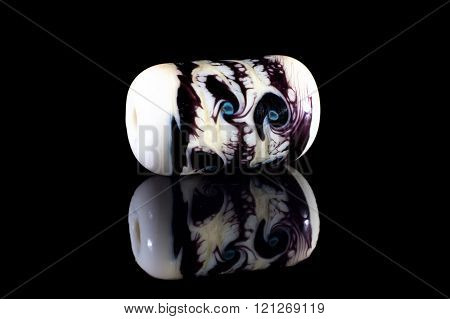 White glassy bead with reflection