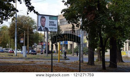 KHARKOV, UKRAINE - CIRCA OCTOBER 2015: A billboard with a portrait of the candidate in mayors near the road on the background of the workshop in the park for dogs walking. In the foreground a sign -