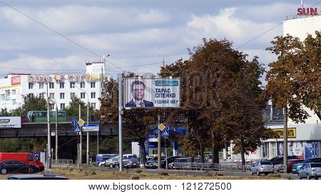 KHARKOV, UKRAINE - CIRCA OCTOBER 2015: Billboard with portrait of candidate for mayor near the highway on the background of the bridge, cars, a business centre, autumn trees and autumn sky.