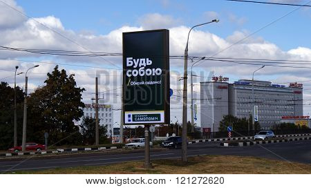 KHARKOV, UKRAINE - CIRCA OCTOBER 2015:  A billboard in the form of a stele with the slogan near the highway on the background of the traffic, a business centre and autumn sky.