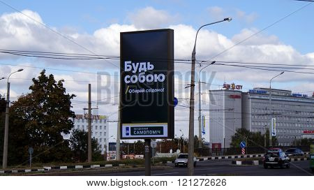 KHARKOV, UKRAINE - CIRCA OCTOBER 2015: A billboard in the form of a stele with the slogan near the highway on the background of the business center and autumn sky.
