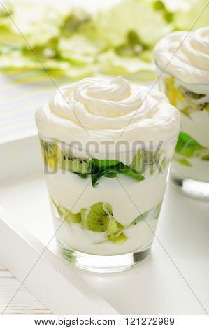 Healthy yogurt dessert with kiwi fruit, jell and cream in glass on white wooden tray.