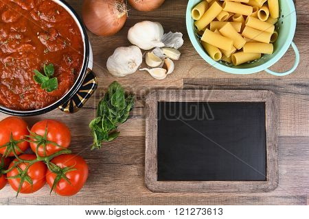 Top view of ingredients for an Italian Meal. Horizontal format with a blank chalkboard.