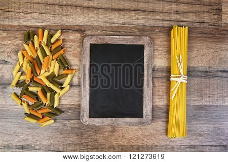 Top view of colorful rigatoni pasta and spaghetti with a blank chalkboard.