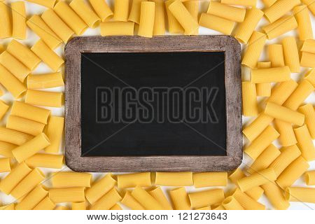 Chalkboard surrounded by rigatoni pasta. Top vies filling the frame.