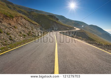 Driving on an empty mountain road towards the sun