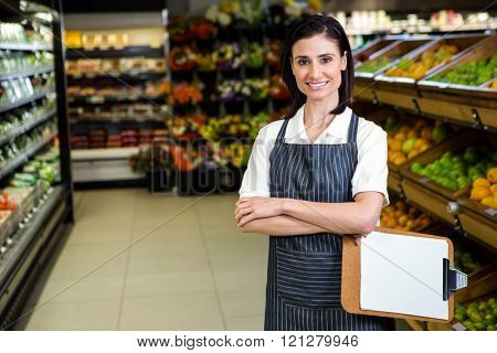Pretty brunette woman taking note in aisle in supermarket