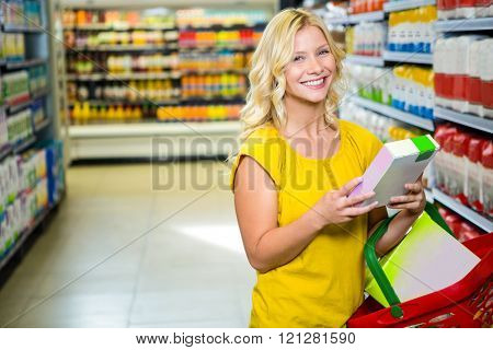 Smiling woman holding a box in supermarket