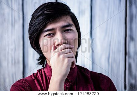 Hipster yawning with his hand over his mouth on wooden background