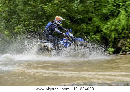 Yuzhno-Sakhalinsk , Russia - August 13, 2015: motorcycle Enduro moves across the river in the forest