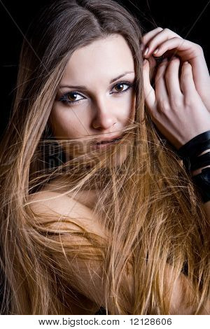 Beautiful fashion model posing on black with wind in her long hair