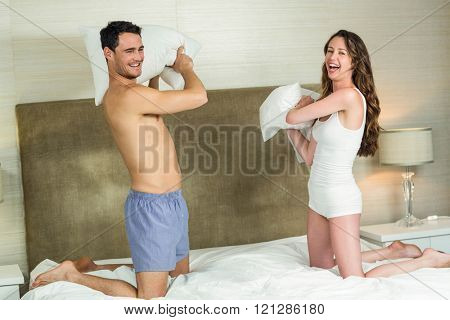Young couple playing pillow fight on bed in bedroom