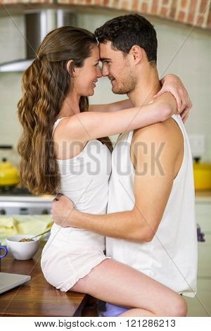 Close-up of romantic young couple cuddling on kitchen worktop