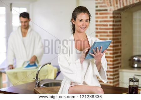 Portrait of beautiful woman in bathrobe sitting on kitchen worktop and using digital tablet while man ironing clothes behind her