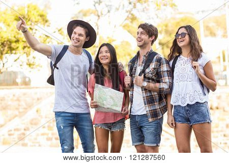 Hip friends going on a walk and checking map in the streets
