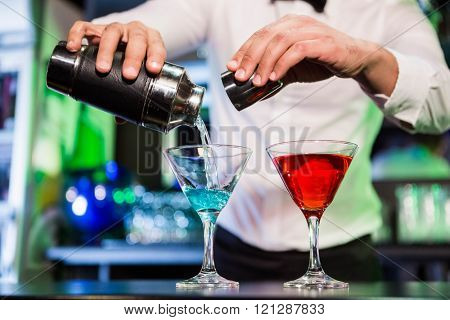 Bartender pouring cocktail from shaker into glasses at bar counter in bar