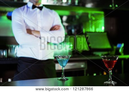 Two glasses of cocktail on bar counter and bartender standing in background