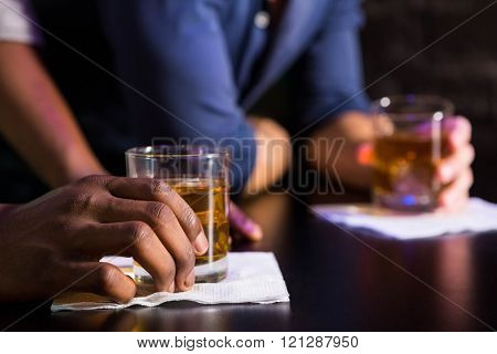 Two men having whiskey at bar counter in bar