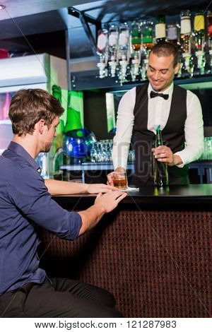 Bartender serving whiskey to man at bar counter in bar