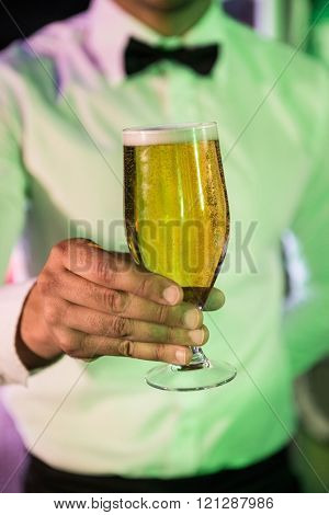 Close-up of bartender serving glass of beer at bar counter in bar