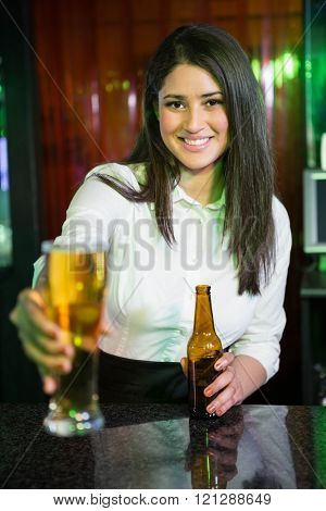 Portrait of pretty bartender serving beer at bar counter in bar