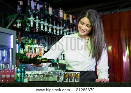Pretty bartender pouring tequila into glasses at bar counter