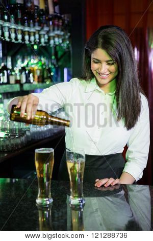 Pretty bartender pouring beer into glasses at bar counter