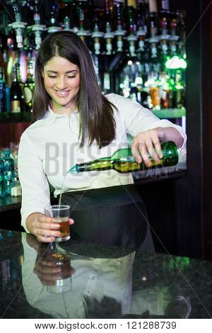 Pretty bartender pouring whiskey in a glass at bar counter