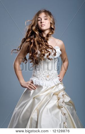 Slim beautiful woman with long hair wearing luxurious wedding dress over gray studio background