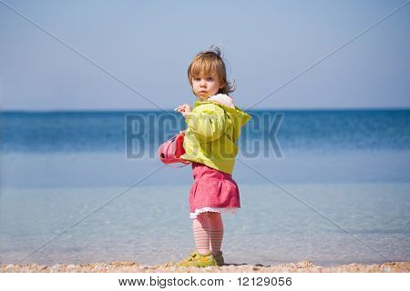 Little baby girl staying on sea coast holding kid bucket and looking at camera