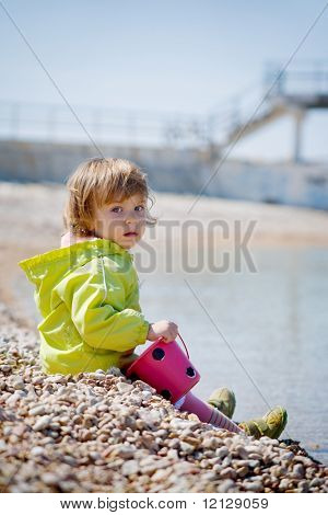 Baby sitting on pebble sea coast with kid bucket and looking at camera