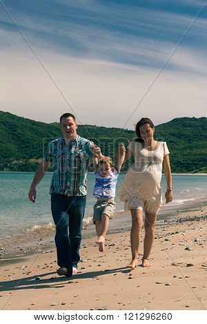 Happy Family Jumping And Walking On The Coast In Spain