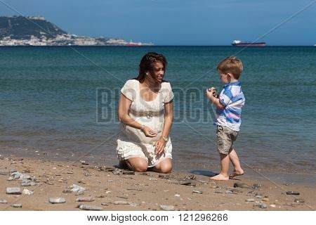 Happy Pregnant Woman Playing With Child Boy On The Beach