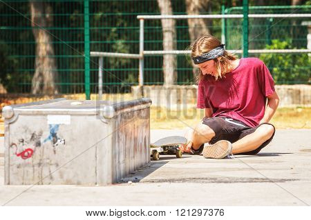 Teenage Boy With Skateboard In The Skate Park