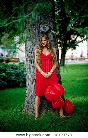 Beautiful woman in red dress staying near tree holding bunch of balloons-hearts and smiling