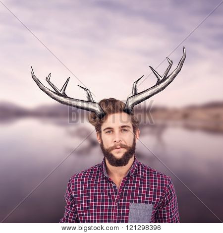 Portrait of confident hipster with clenched fist against lake