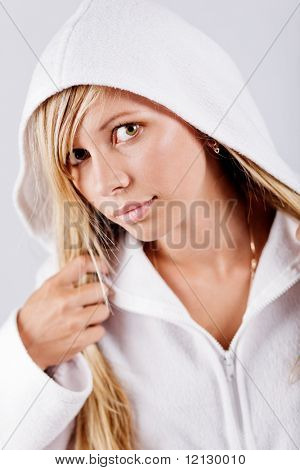 Blond swarthy woman wearing white fleece hoodie posing at studio