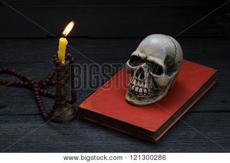 Still life photography with human skull and mala on wood background