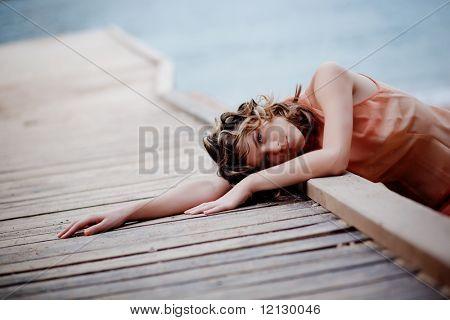 Traurige Frau liegend auf Liegeplatz gegenüber dem Meer Hintergrund