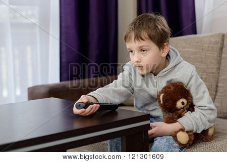 7 Year Old Boy Sitting On The Sofa And Watching Tv.