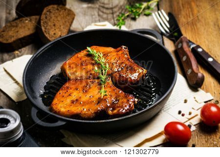 Grilled pork chops in sweet honey glaze, served in grill iron skillet with fresh thyme, rye bread an