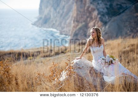 Beautiful bride sitting on stone at field over mountains and sea coast landscape