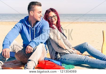 Young Couple On The Beach Sitting Back To Back In A Sunny Spring Day - Love And Tenderness  Concept
