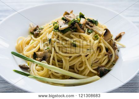 Pasta With Mushrooms And Green Onions On A White Plate