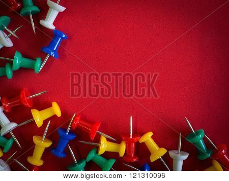 Colorful thumbtack pinned frame on red rough leather for copy space