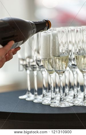 Waiter pouring champagne in the party