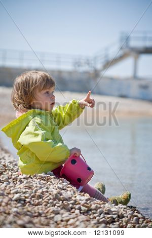Child sitting os sea coast and showing by finger at smth