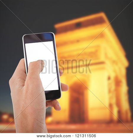 Cropped hand of man using mobile phone against arc de triumphe in france