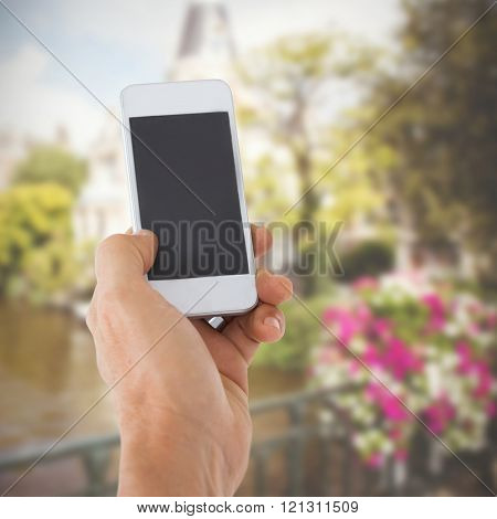 Male hand holding a smartphone against canal in amsterdam