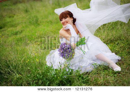 Novia feliz posando sobre hierba en primavera
